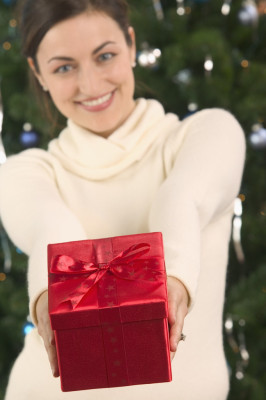 Young Woman Offering Elegantly Wrapped Christmas Present --- Image by © Royalty-Free/Corbis