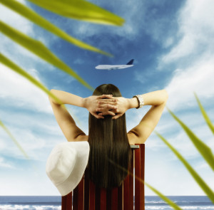 Young woman watching airplane fly by from tropical beach --- Image by © Royalty-Free/Corbis