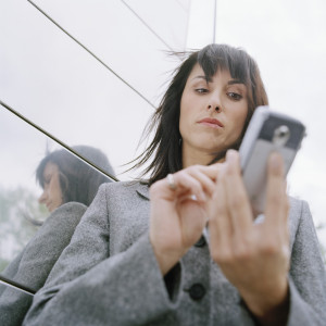 Business woman standing outside in front of office building, using mobile phone